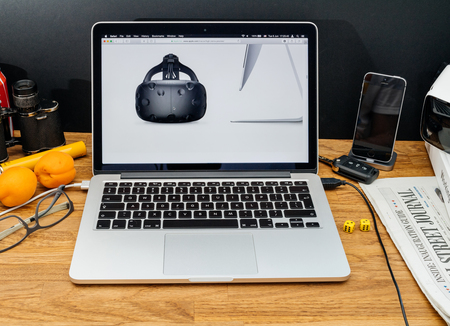 htc: PARIS, FRANCE - JUNE 6, 2017: Apple Computers website on MacBook Retina in creative environment showcasing latest macOS High Sierra from Apple at WWDC 2017 - HTC vive vr headset with new iMAc