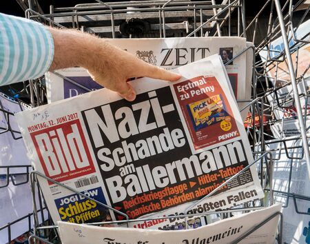 am: PARIS, FRANCE - JUN 12, 2017: Man point of view personal perspective buying at press kiosk German newspaper with reactions nazi schande am Ballermann