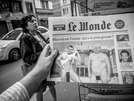 first day: PARIS, FRANCE - JUN 12, 2017: Man point of view personal perspective buying at press kiosk French newspaper Le Wonde with reactions to French legislative election, 2017 a day after first round