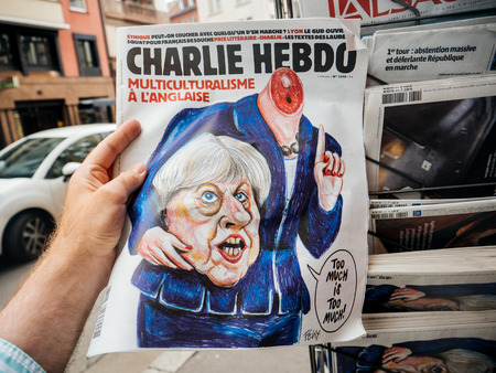 without people: PARIS, FRANCE - JUN 12, 2017: Man point of view personal perspective buying at press kiosk satire newspaper Charlie Hebdo with Theresa May without head caricature with reactions to United Kingdom general election of 2017 - May fights to remain PM Editorial