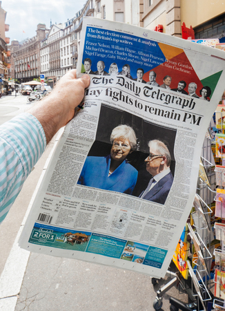 PARIS, FRANCE - JUN 12, 2017: Man point of view personal perspective buying at press kiosk The Daily Telegraph newspaper with reactions to United Kingdom general election of 2017 - Theresa May fights to remain PM