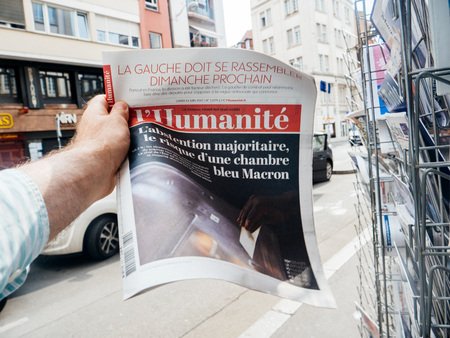 first day: PARIS, FRANCE - JUN 12, 2017: Man point of view personal perspective buying at press kiosk French newspaper LHumanite with reactions to French legislative election, 2017 a day after first round