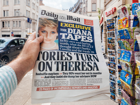 PARIS, FRANCE - JUN 12, 2017: Man point of view personal perspective buying at press kiosk Daily Mail newspaper Princessa Diana secret Tapes scandal and Theresa May elections in UK