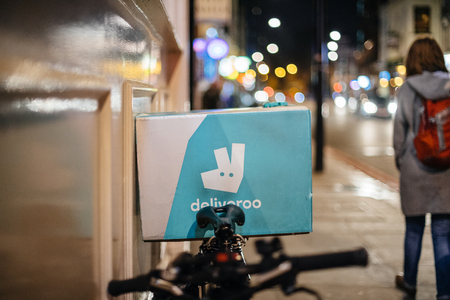 LONDON, UNITED KINGDOM - MAR 3, 2018: Deliveroo delivery bike in city  of London. Deliveroo is a British online food delivery company with operations spread across eighty-four cities in the UK, the Netherlands, France, Germany, Belgium, Ireland, Spain, It