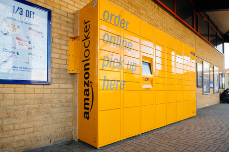 OXFORD, UNITED KINGDOM - MAR 2, 2017: Side view of Amazon locker orange delivery package locker in public place at the train station in Oxford - Amazon Locker is a self-service parcel delivery service offered by online retailer Amazon.com.