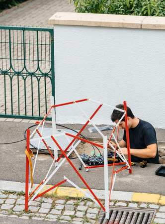 PARIS, FRANCE - JUL 12, 2017: Worker inside sewage manhole hole - telecomunication internet provider company working on implementation of fiber optic cables in sewage system using fiber optic welding machine Editorial