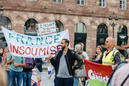 populist: STRASBOURG, FRANCE - JUL 12, 2017: Protesters with placards at protest against Macron government spending cuts and pro-business tax and labor reforms