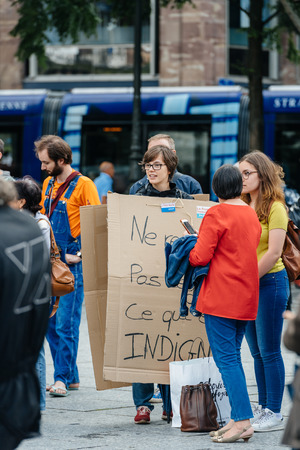 populist: STRASBOURG, FRANCE - JUL 12, 2017: Woman wearing placard at protest against Macron government spending cuts and pro-business tax and labor reforms Editorial