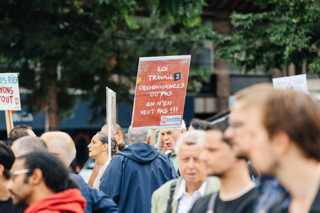 populist: STRASBOURG, FRANCE - JUL 12, 2017: Young and senior people with placards at protest against Macron government spending cuts and pro-business tax and labor reforms