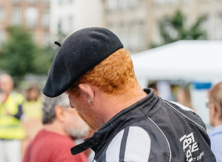 populist: STRASBOURG, FRANCE - JUL 12, 2017: Redhead man wearing French hat at protest  against Macron government spending cuts and pro-business tax and labor reforms