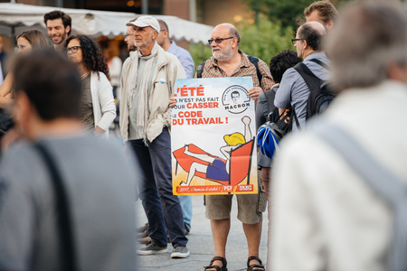 STRASBOURG, FRANCE - JUL 12, 2017: Senior man with placard in Place Kleber as Melenchon called for day of protest against Macron government spending cuts and pro-business tax and labor reforms