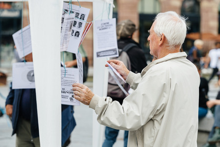 populist: STRASBOURG, FRANCE - JUL 12, 2017: Senior man reading manifest by Melenchon as he called for day of protest against Macron government spending cuts and pro-business tax and labor reforms
