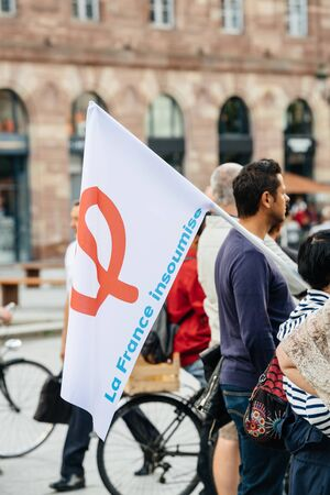 populist: STRASBOURG, FRANCE - JUL 12, 2017: Phi sign on flag - Protesters in city as Melenchon called for day of protest against Macron government spending cuts and pro-business tax and labor reforms