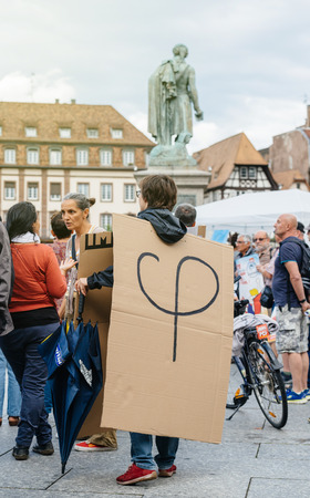 populist: STRASBOURG, FRANCE - JUL 12, 2017: Phi logo of Melenchon on cardboard on protesters in city at protest against Macron government spending cuts and pro-business tax and labor reforms Editorial
