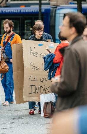 STRASBOURG, FRANCE - JUL 12, 2017: Woman wearing placard at protest against Macron government spending cuts and pro-business tax and labor reforms Editorial
