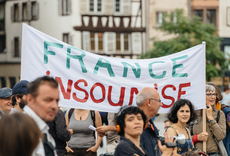 populist: STRASBOURG, FRANCE - JUL 12, 2017: France Insoumise placard at protest against Macron government spending cuts and pro-business tax and labor reforms Editorial