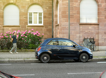 STRASBOURG, FRANCE - MAY 30, 2017: Blue Fiat 500 Riva parked in the city with nearby passing senior man admiring the beautiful car. This is a special edition of the facelift Fiat 500 that showcases the Riva yacht brand, which is owned by the Ferretti Grou