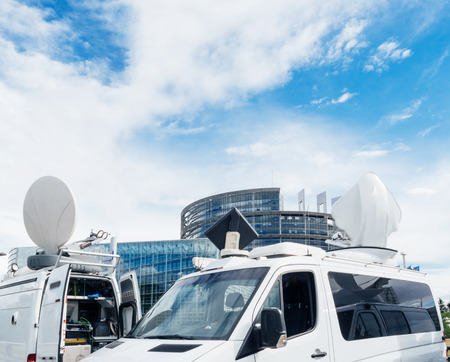 TV Media Television Trucks with multiple Satellite parabolic antennas and fiber optic cables preparing to report live the official European Ceremony debate meeting