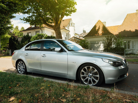 silver background: KEHL, GERMANY - JUL 14, 2017: Silver BMW luxury limousine sedan parked in city with luxury real estate building in the background beautiful german house