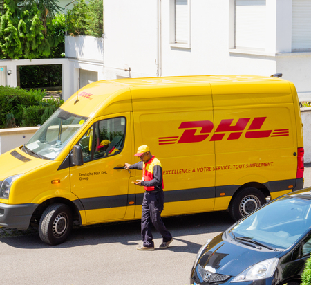 PARIS, FRANCE - MAY 29, 2017: Courier enters DHL yellow delivery van after delivering the on time delivering package parcel and looking in his smartphone communicator device where to deliver the next parcel