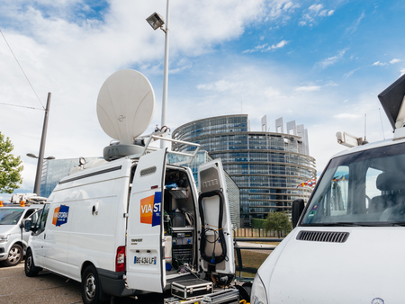 STRASBOURG, FRANCE - JUN 30, 2017: Via storia TV Media Television Trucks with multiple Satellite parabolic antennas and fiber optic cables preparing to report live the official European Ceremony of Honour for Dr. Helmut Kohl at European Parliament