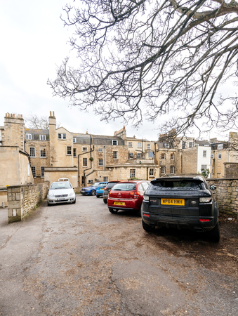 BATH, UNITED KINGDOM - MAR 7, 2017: Typical Bath England architecture real estate houses with cars parked in he courtyard