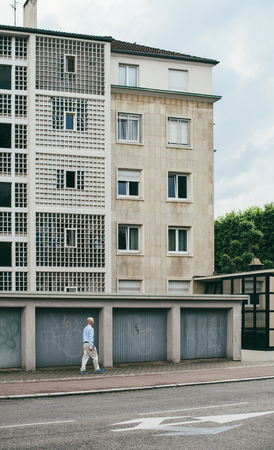 STRASBOURG, FRANCE - MAY 30, 2017 Bald man walking near the garage doors with social building Banlieue in the background