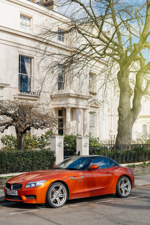 LONDON, UNITED KINGDOM - MAR 9, 2017: Luxury red BMW Z4 parked in front of luxury mansion in London in expensive neighborhood on a warm summer day. Z4 rear-wheel drive sports car by the German car maker BMW.