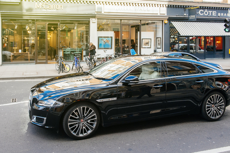 LONDON, UNITED KINGDOM - MAR 9, 2017: Luxury new black Jaguar XJ AUTOBIOGRAPHY LWB driving on the crowded london street with open shoppings and commerces in the background.