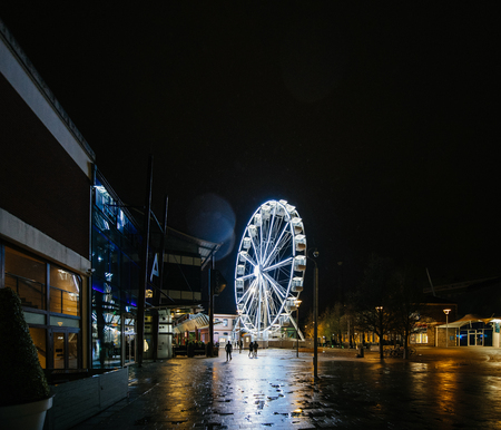 Sky View Observation Wheel in Anchor Square in central Bristol at night with people silhouette walking nearby on a rainy day