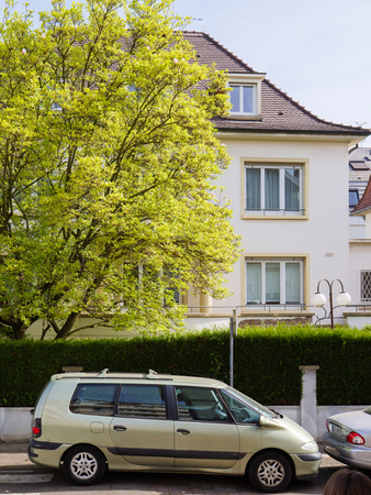 STRASBOURG, FRANCE - APR 12, 2017: Renault Scenic Espace mini van car parked on the French street under large tree and beautiful house behind