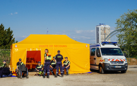 STRASBOURG, FRANCE - APR 28, 2017: Premier Secours - First Aid van parked on the city street with safety workers surveying the zone nearby public open space event