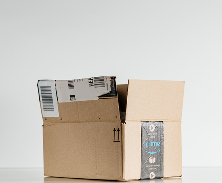 PARIS, FRANCE - JUL 30, 2017: Open Amazon Prime logotype printed on cardboard box side. Amazon is an American electronic e-commerce company distribution worlwide e-commerce goods