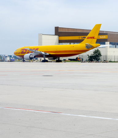 recibo: FRANKFURT, GERMANY - AUG 8, 2017: Yellow Airbus A300-600 serving DHL parcel delivery company loading and unloading parcels for delivery on time a the Frankfurt Airport Cargo zone