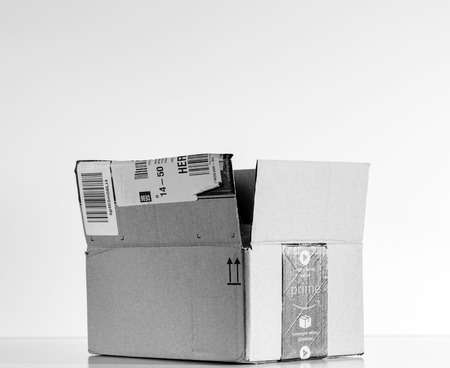PARIS, FRANCE - JUL 30, 2017: Black and white of open Amazon Prime logotype printed on cardboard box side. Amazon is an American electronic e-commerce company distribution worlwide e-commerce goods Editorial