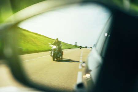 Driver looking in the rear view mirror of a defocused motorcycle driver  - keeping distance and securing the driving process