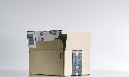 PARIS, FRANCE - JUL 30, 2017: Open Amazon Prime cardboard box side. Amazon is an American electronic e-commerce company distribution worlwide e-commerce goods