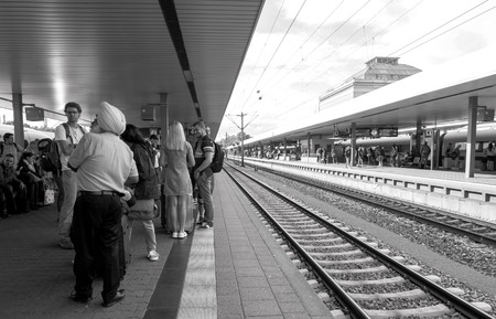 freight train: MANNHEIM, GERMANY - AUG 8, 2017: Large group of people including Indian tourist wearing turban waiting at the train station platform in Mannheim hauptbahnhof Train station commuting in German Editorial