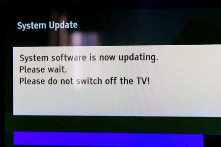 System update software process on a modern television set in living room with message System software is now updating, please wait. Please do not switch off your tv. Tilt-shift lens used 스톡 콘텐츠