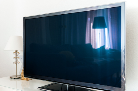 Large modern 4k tv plasma screen in living room vith no siganl blue screen, reflection of the living room inside Stock Photo