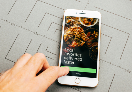 PARIS, FRANCE - SEP 26, 2016: Male hand holding New Apple iPhone 7 Plus after unboxing and testing by installing the app application software Uber eats food delivery app Redactioneel