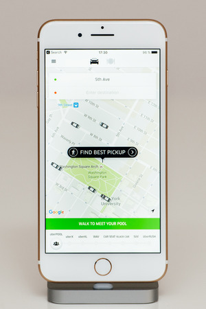 PARIS, FRANCE - SEP 26, 2016: New Apple iPhone 7 Plus in docking station after unboxing and testing by installing and running the app application software find best pickup Uber app at 5th Avenue in New York