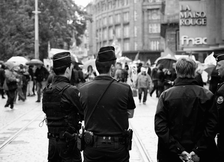 STRASBOURG, FRANCE - SEPT 12, 2017: Police under rain surveillance of people at political march during a French Nationwide day of protest against the labor reform proposed by Emmanuel Macron Government Editorial