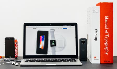 PARIJS, FRANKRIJK - 3 SEP 2017: Minimalistische creatieve kamertafel met Safari-browser open op MacPook Pro-laptop presentatie van Apple Computers-website met nieuwste iPhone X 10 volgende ot Apple Watch en Air Pods opladen op luchtlader