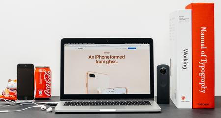 PARIJS, FRANKRIJK - 3 SEP 2017: Minimalistische creatieve kamertafel met Safari Browser open op MacPook Pro-laptop met presentatie van Apple Computers-website met nieuwste iPhone 8 en 8 Plus met glasvormen Redactioneel