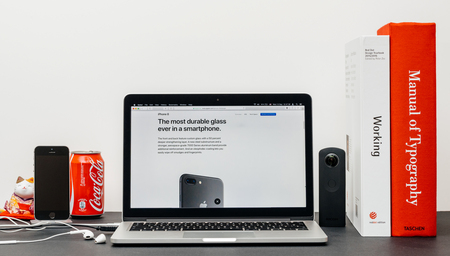 PARIS, FRANCE - SEP 3, 2017: Minimalist creative room table with Safari Browser open on MacPook Pro laptop showcasing Apple Computers website with latest iPhone 8 and 8 Plus with durable glass Editorial