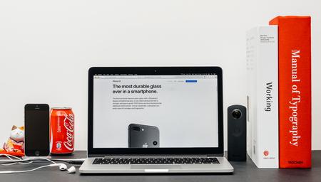 PARIS, FRANKRIJK - SEP 3, 2017: Minimalistische creatieve kamertafel met Safari Browser open op MacPook Pro laptop met Apple Computers website met de nieuwste iPhone 8 en 8 Plus met duurzaam glas