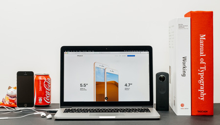 PARIS, FRANCE - SEP 3, 2017: Minimalist creative room table with Safari Browser open on MacPook Pro laptop showcasing Apple Computers website with latest iPhone 8 and 8 Plus display size inch