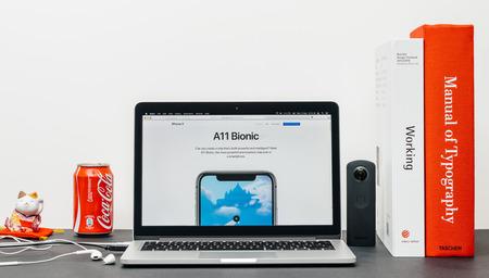 PARIJS, FRANKRIJK - 3 SEP 2017: Minimalistische creatieve kamertafel met Safari Browser open op MacPook Pro-laptop met presentatie van de Apple Computers-website met de nieuwste iPhone X 10 met A11 Bionic Chip