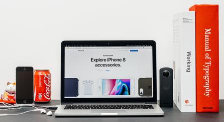 PARIJS, FRANKRIJK - 3 SEP 2017: Minimalistische creatieve kamertafel met Safari Browser open op MacPook Pro-laptop met presentatie van de Apple Computers-website met de nieuwste iPhone 8 en 8 Plus met accessoires Redactioneel